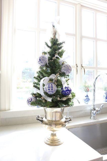 un albero di Natale da tavolo in un'urna vintage, con fiocchi di nastro bianco e ornamenti natalizi blu e bianchi è un'idea adorabile e vintage