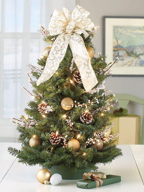 un albero di Natale da tavolo decorato con luci, salice, pigne innevate, un bellissimo fiocco decorato in cima e ornamenti d'oro