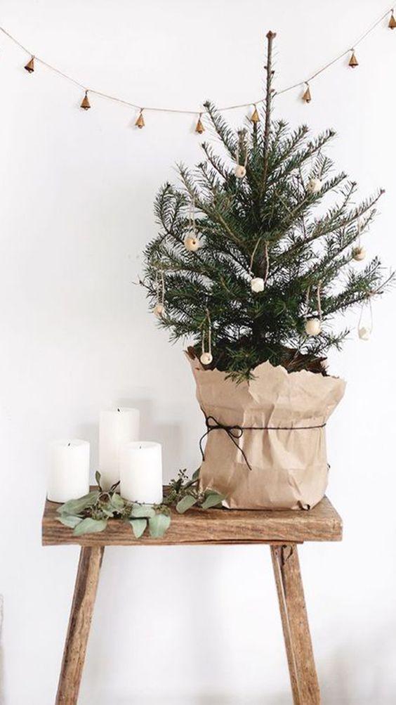 un albero di Natale da tavolo decorato con perline di legno e avvolto con carta è un'idea carina con un tocco nordico