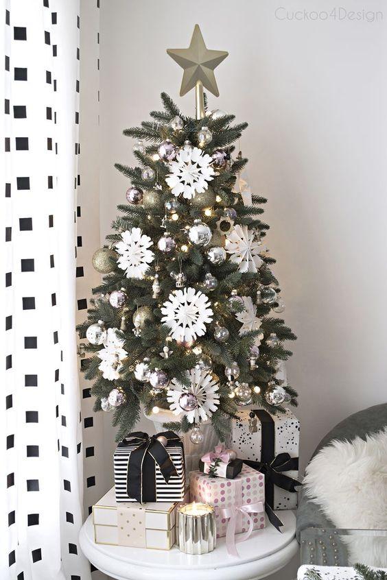 un elegante albero di Natale monocromatico con ornamenti in argento e oro, fiocchi di neve bianchi e luci più un cappello a cilindro stella