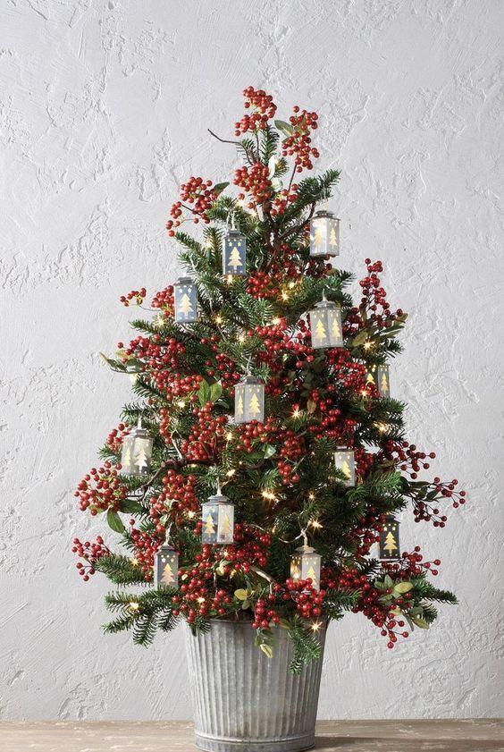 un albero di Natale da tavolo di ispirazione vintage con bacche, luci e mini lanterne a forma di albero è un'idea adorabile e audace