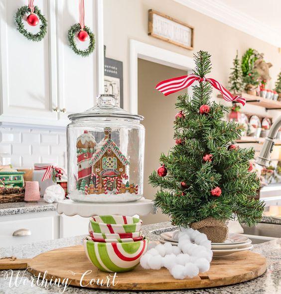 un albero di Natale da tavolo in tela, con ornamenti rossi, un nastro a strisce rosse e bianche in cima è un'idea adorabile e chic