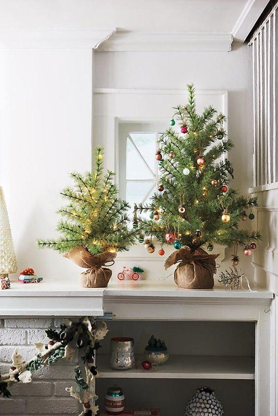 graziosi alberi di Natale da tavolo - uno decorato con luci, un altro con piccoli ornamenti colorati e luci