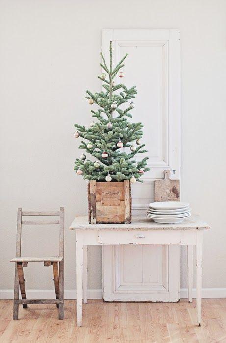 un albero di Natale da tavolo in una scatola di legno e con ornamenti a blocchi di colore pastello sembra un po 'retrò e un po' rustico