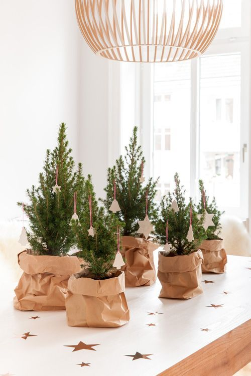 una disposizione di mini alberi di Natale da tavolo in sacchi di carta e con ornamenti di argilla bianca sono belli e semplici