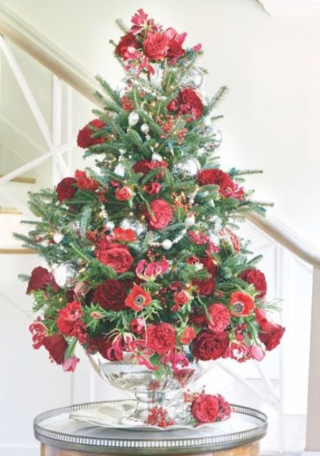 L'esclusivo decoro dell'albero di Natale da tavolo fatto con bacche rosse, fiori rossi e bordeaux e alcuni ornamenti d'argento è chic e glam
