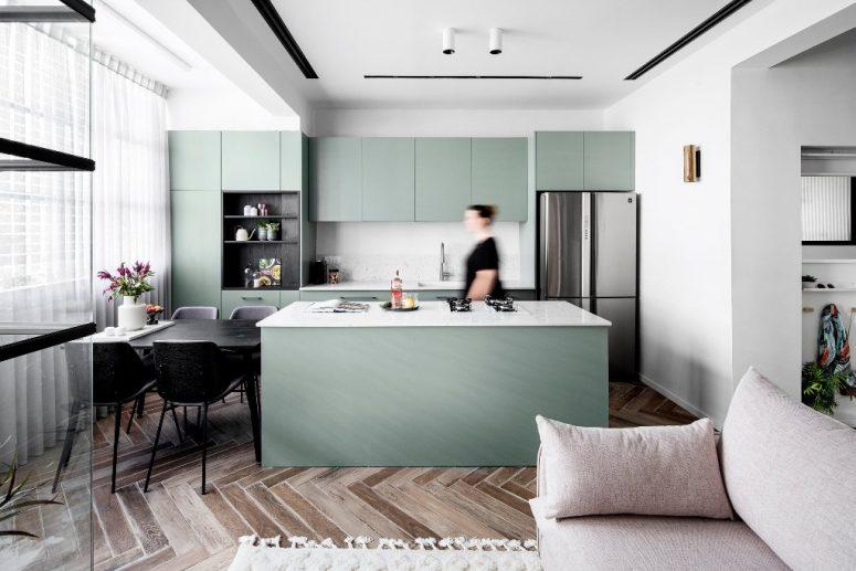 Anche la cucina e la zona pranzo sono qui, gli armadi sono verdi, con ripiani in marmo e alzatina, tavolo da pranzo nero e sedie