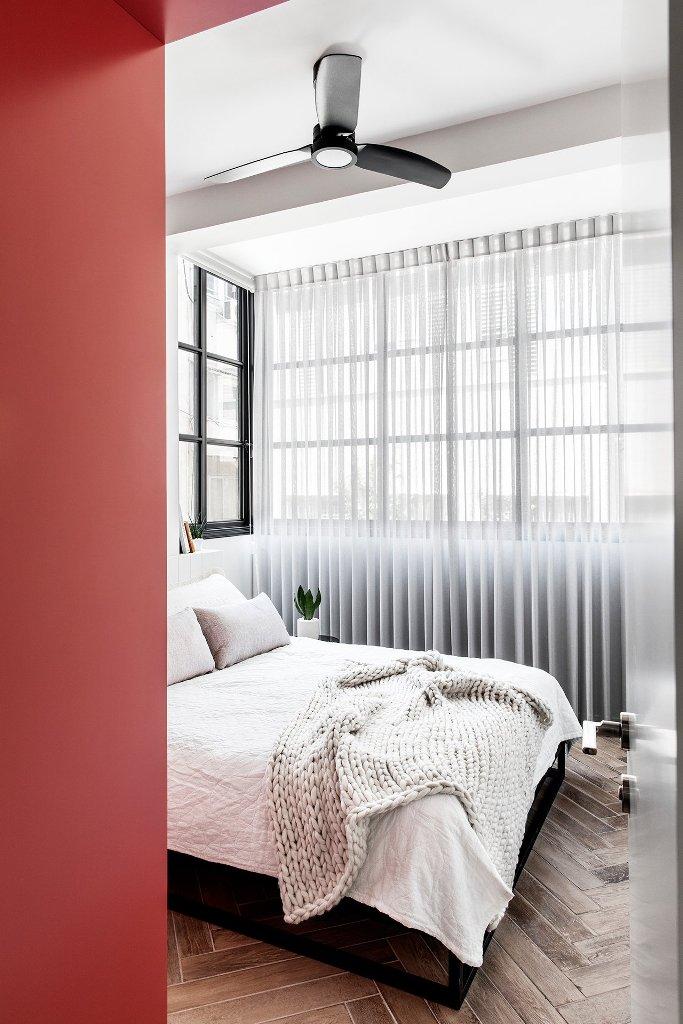 La camera da letto è inondata di luce e presenta solo i mobili più necessari e un accento rosso