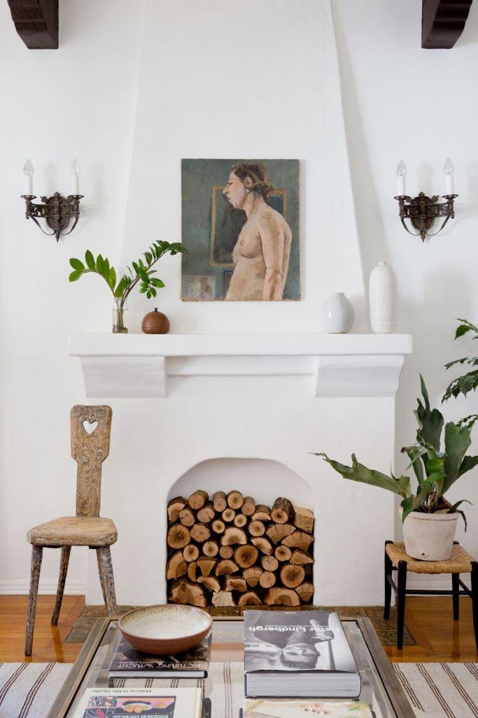 un elegante caminetto bianco non funzionante con all'interno legna da ardere molto naturale è un'idea chic con un tocco rustico