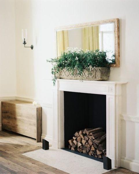 un camino vintage e raffinato con una mensola bianca e legna da ardere all'interno più una fioriera con vegetazione e fiori per uno spazio chic