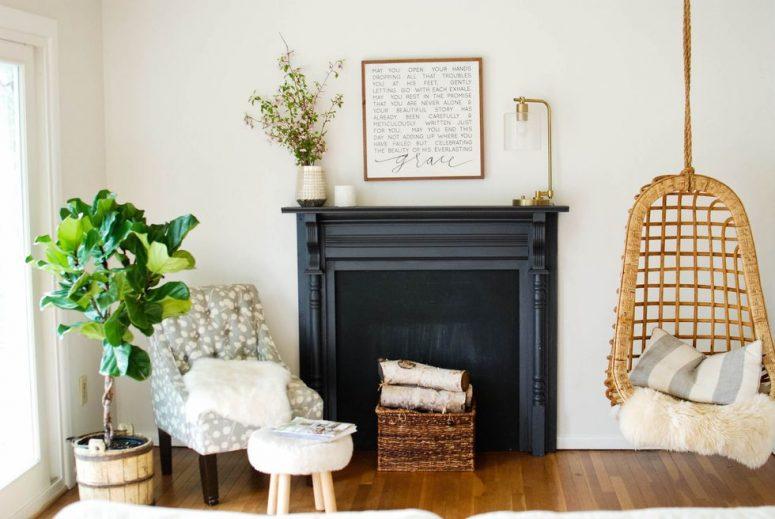 un finto camino nero con una raffinata mensola del camino, un cesto con tronchi di legno è un'idea rustica ed elegante da scegliere