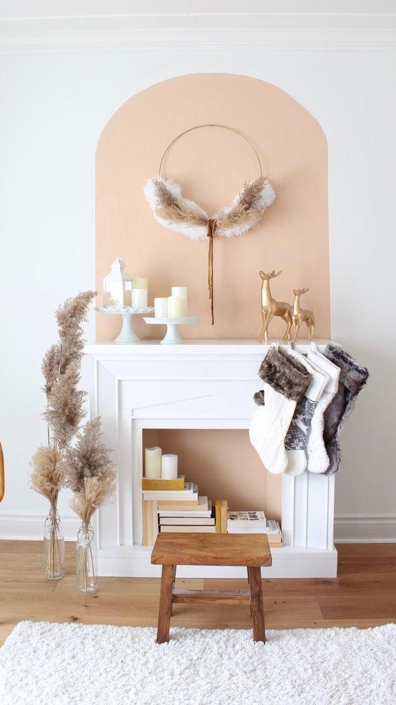 un finto caminetto con l'interno color pesca, libri, candele e calze e una ghirlanda per Natale
