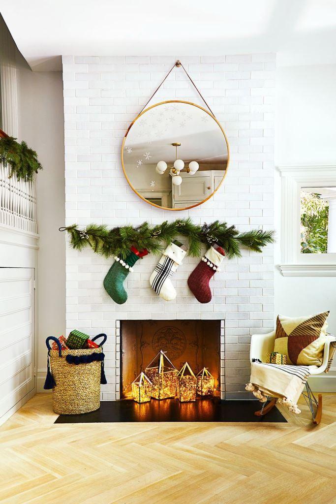 un caminetto non funzionante in stile natalizio con delle calze appese sopra e con delle lanterne luminose al suo interno