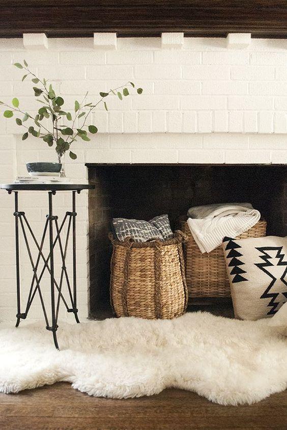 un camino in mattoni bianchi con cesti con cuscini e plaid, ecopelliccia bianca per un accogliente spazio della fattoria