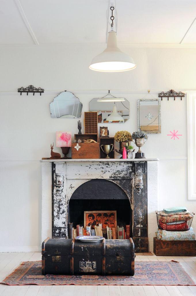 uno squallido camino cihc con libri e un'opera d'arte audace sembra simile a una dichiarazione e audace, una valigia di fronte aggiunge fascino vintage