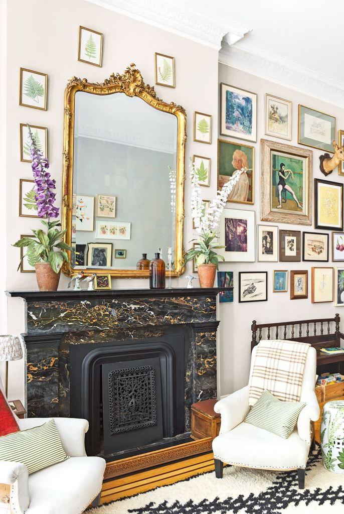 un raffinato camino nero, bianco e oro con una bella e raffinata copertura e uno splendido specchio vintage sopra