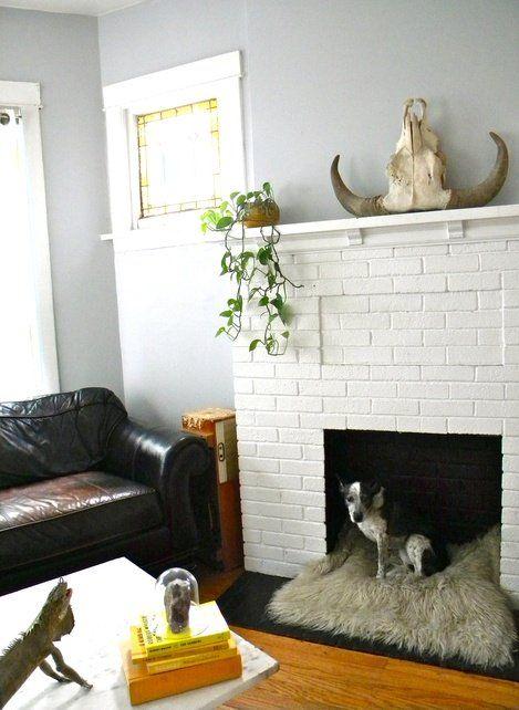 un caminetto in finto mattone bianco con un accogliente letto per cani sfocato all'interno è un ottimo modo per usare un caminetto non funzionante
