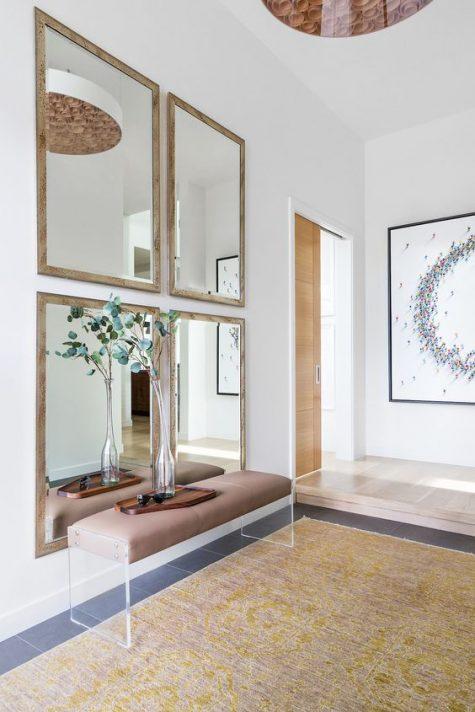 un ingresso moderno chic con una galleria di specchi, una panca in pelle e acrilico e vegetazione in un vaso