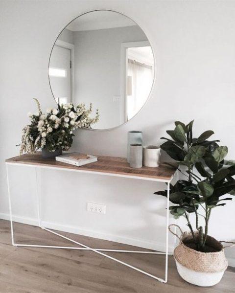 un ingresso moderno chic con una console in legno, uno specchio rotondo e alcune piante e vasi in vaso