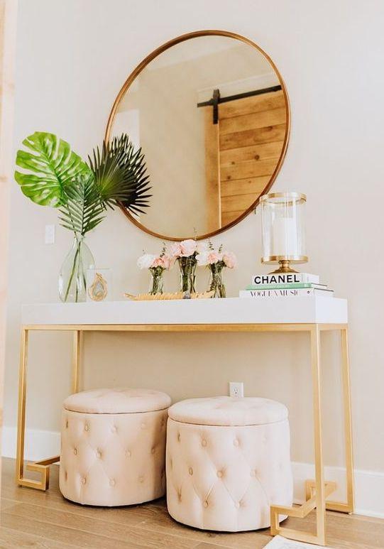 un favoloso ingresso moderno con una console bianca, pouf portaoggetti arrossati, uno specchio rotondo e una candela