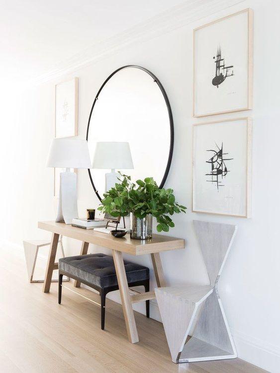 un ingresso moderno con uno specchio rotondo, una consolle in legno, un pouf imbottito, sedie geometriche e verde abbinate