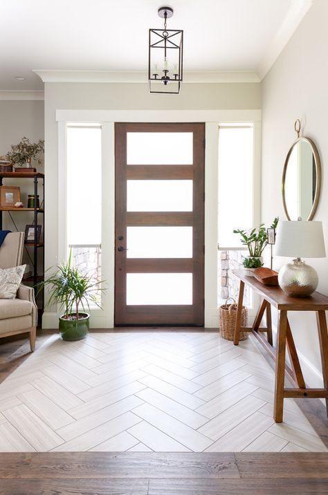 un ingresso moderno e semplice con una consolle simile a una panchina, piante in vaso, uno specchio rotondo e un cestino