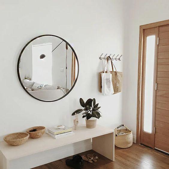 un ingresso moderno con una panca elegante, uno specchio rotondo, alcuni cestini e un appendiabiti è elegante e sembra etereo