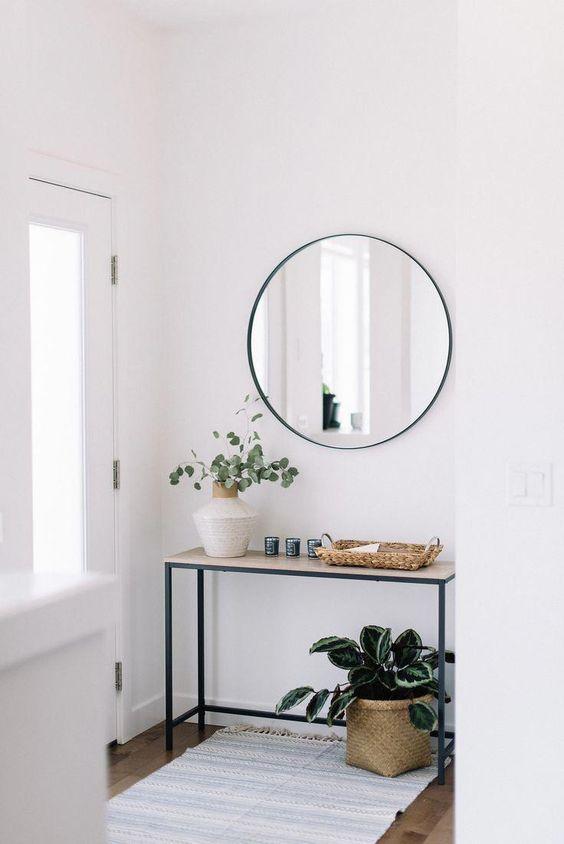 un ingresso frontale moderno con una console stretta, uno specchio rotondo, piante in vaso e cesti è molto accogliente