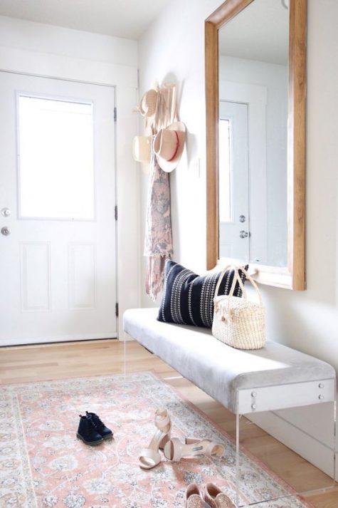 un ingresso moderno e luminoso con una panca con gambe in acrilico, uno specchio, un tappeto boho e un appendiabiti