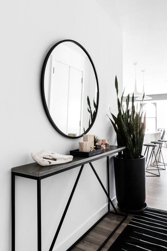 un ingresso moderno con una console stretta nera, uno specchio rotondo, una pianta importante e un po 'di arredamento
