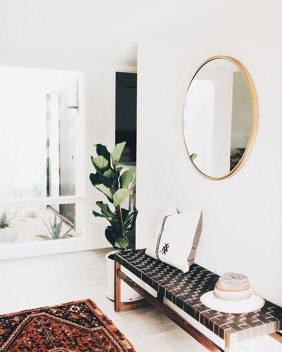 un ingresso moderno con una panca intrecciata in pelle, un tappeto boho e uno specchio rotondo oltre a una pianta d'effetto