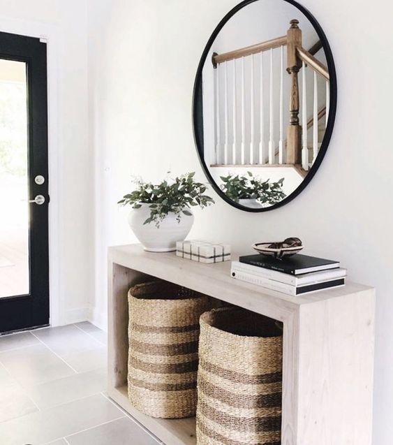 un ingresso moderno con un'elegante consolle in legno, cestini per la conservazione, uno specchio rotondo e una pianta in vaso