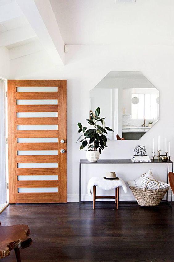 un ingresso semplice e moderno con uno specchio geometrico, una console nera, sgabelli e un cesto con cuscini