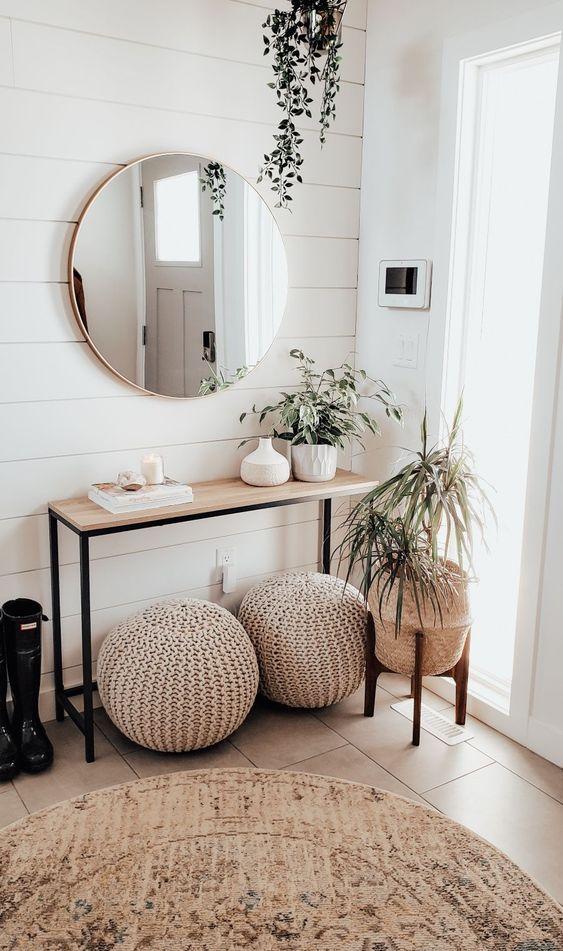 un ingresso moderno neutro con una console in legno, pouf all'uncinetto, piante in vaso e uno specchio rotondo è chic