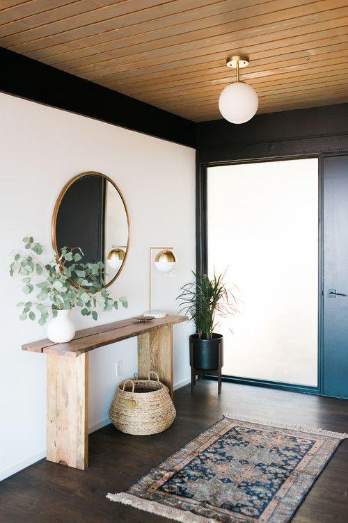 un ingresso moderno ed elegante con uno specchio rotondo, un cestino, una pianta su un supporto e un tappeto boho