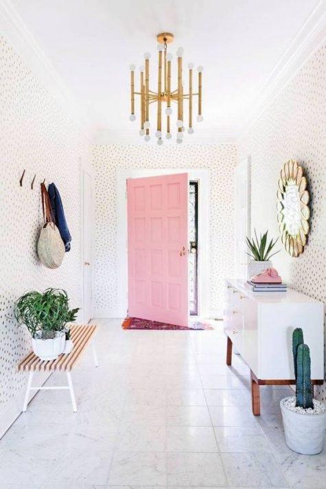 un ingresso moderno giocoso e stravagante con pareti a pois, una credenza bianca, una panca, appendiabiti e uno specchio