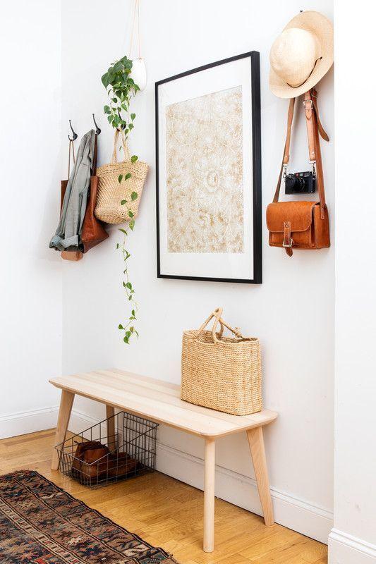 un ingresso semplice e moderno con una panca in legno, un'opera d'arte, un cesto in filo metallico e appendiabiti