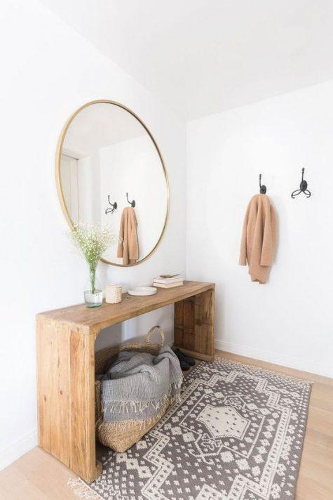 un ingresso moderno dai colori caldi con una panca in legno, uno specchio rotondo, un tappeto stampato e un cestino con una coperta