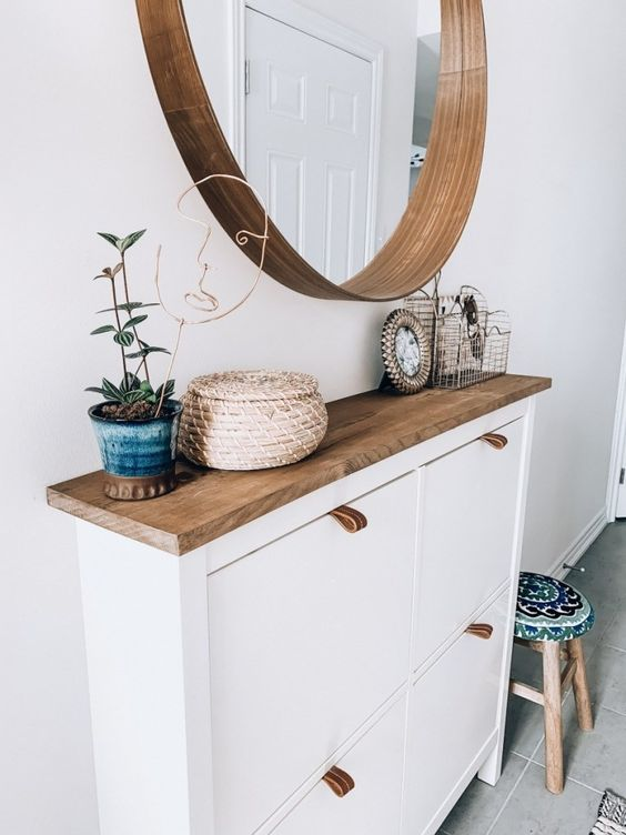 un ingresso moderno ed elegante con una scarpiera IKEA hackerata, uno specchio rotondo e una pianta in vaso