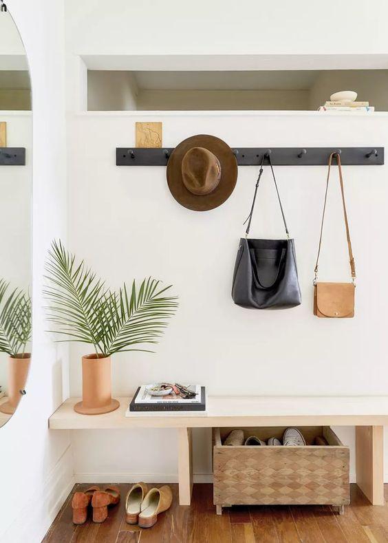 un ingresso moderno ed elegante con una panca elegante, un appendiabiti, una scatola di immagazzinaggio e uno specchio sul muro