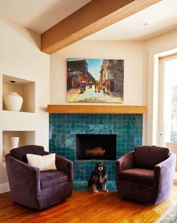 un angolo chic e accogliente con un camino rivestito con piastrelle blu lucide e sedie viola è uno spazio audace decorato con gusto impeccabile
