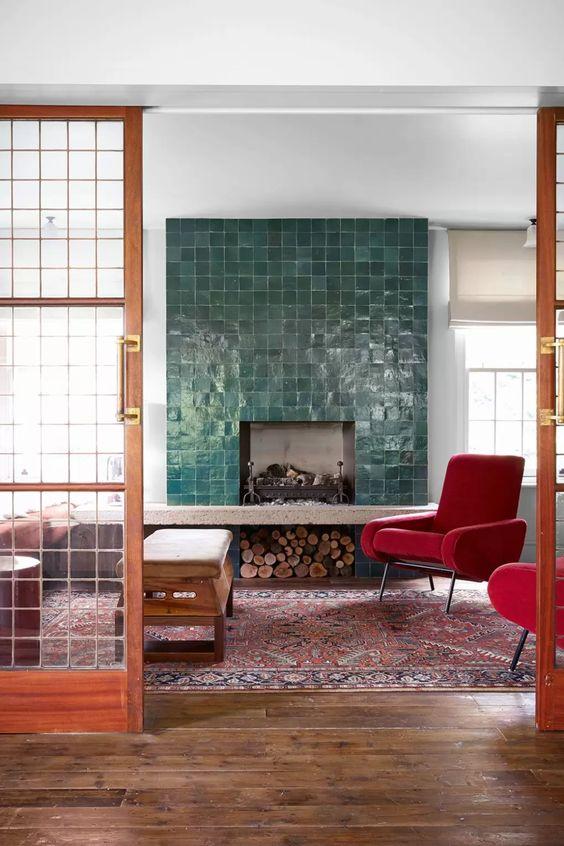 un camino rivestito con piastrelle smaltate verdi e sedie rosse moderne di metà secolo che infondono colore allo spazio e lo rendono accogliente e accogliente