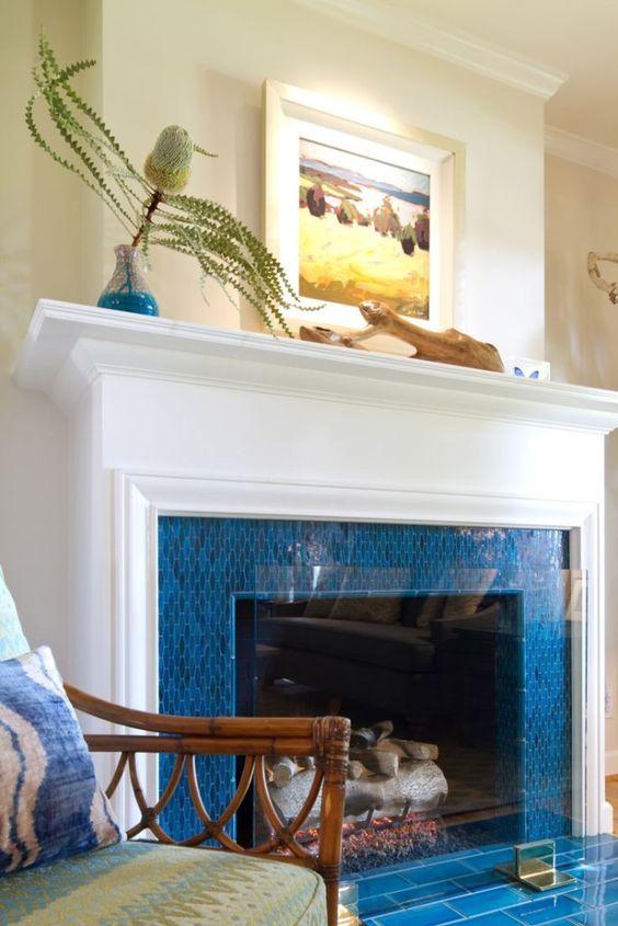 un camino circondato da piastrelle blu brillante, con un'elegante mensola bianca e un po 'di arte costiera è l'ideale per una casa al mare