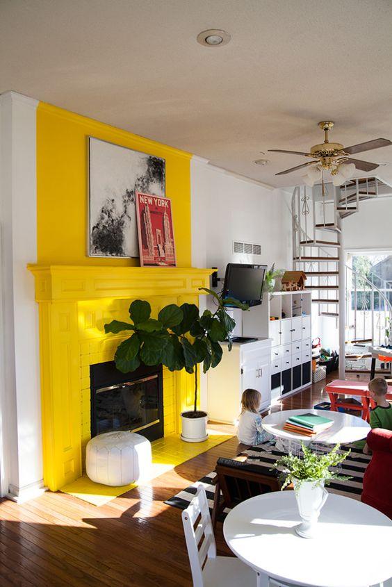 un caminetto giallo solare e una mensola del camino con alcune opere d'arte e una pianta accanto creano un'atmosfera solare e brillante nella stanza