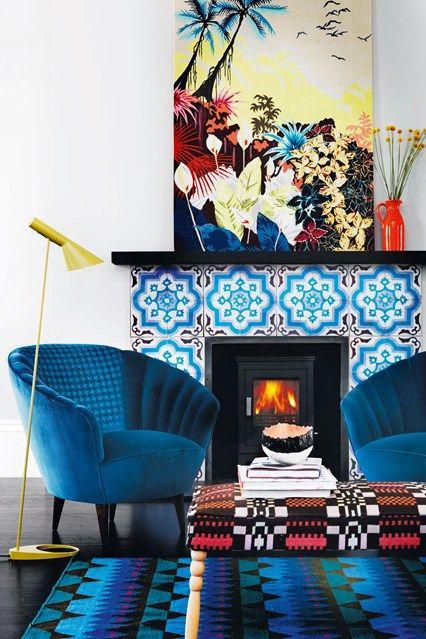 sedie blu elettrico, un tappeto stampato blu brillante, un audace caminetto in piastrelle blu e un'opera d'arte colorata creano colori in abbondanza che miglioreranno il tuo umore
