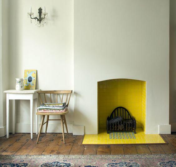 un camino minimalista con piastrelle gialle dentro e fuori porta una sensazione di calore nello spazio e aggiunge un brillante tocco di colore