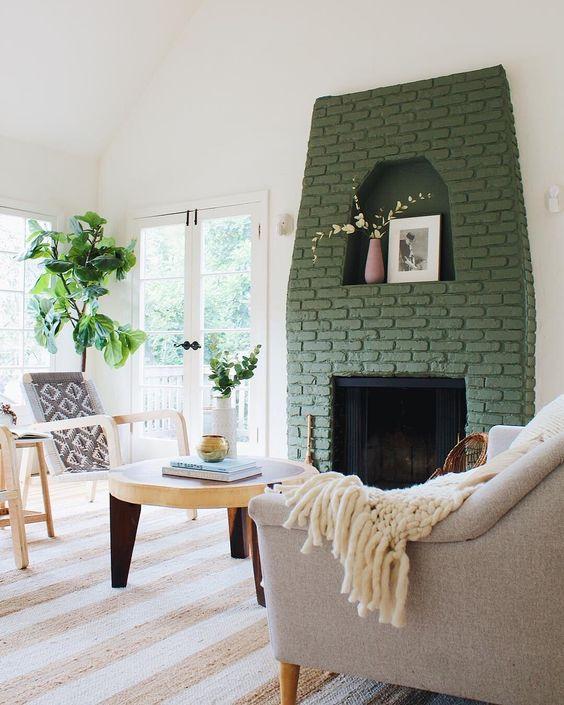 un camino con cornice in mattoni verdi dona colore a questo spazio neutro e lo rende più accattivante e più interessante