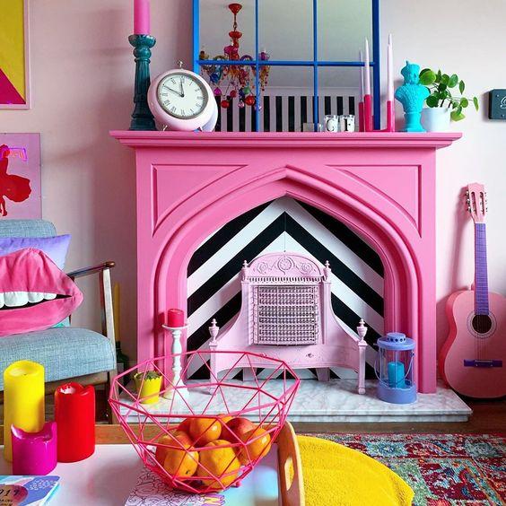 un eccentrico soggiorno colorato rifinito con un finto caminetto rosa caldo con accessori colorati sulla mensola del camino