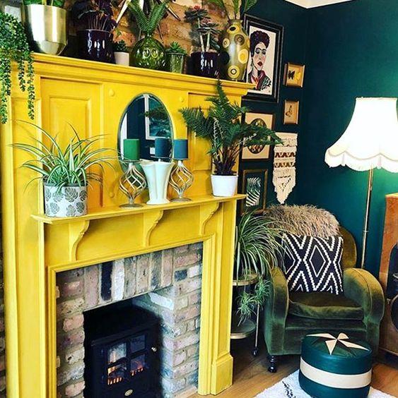 un camino in mattoni con una cornice gialla solare, molte piante e candele è un'idea molto accogliente e una nuova interpretazione di un camino tradizionale