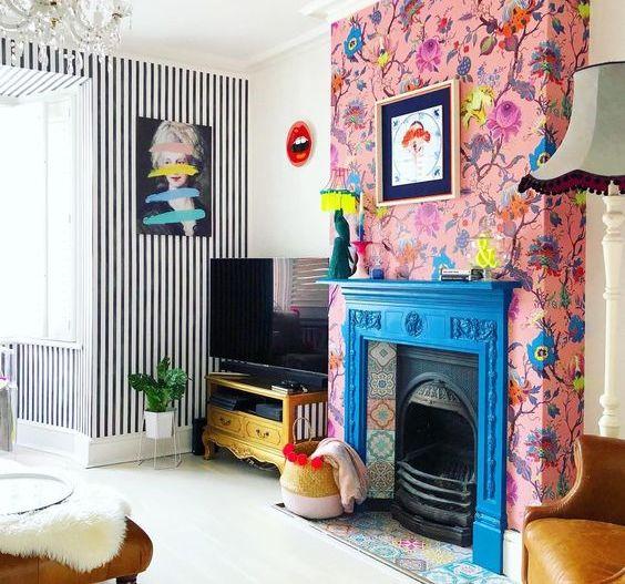 un caminetto blu con piastrelle colorate e carta da parati floreale rosa intorno che accentuano ancora di più il focolare
